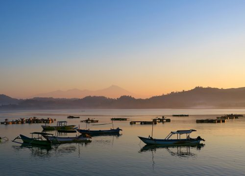 Black fishermans boats silhouettes in the morning at Lombok island, Indonesia.